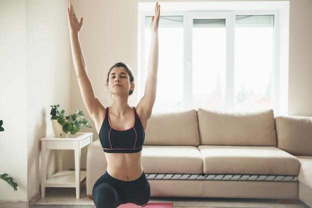 Молодая брюнетка женщина растягивается в своей гостиной и занимается фитнесом дома