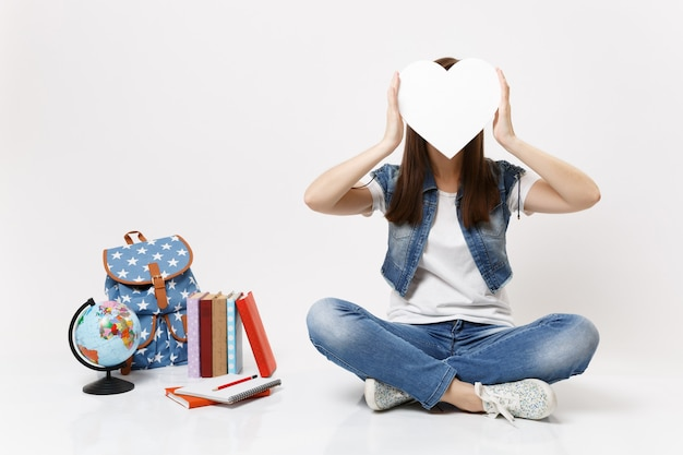 Young brunette woman student covering face with white heart with copy space sitting near globe backpack, school books isolated on white wall