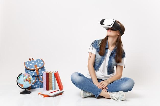Giovane studentessa bruna con occhiali per realtà virtuale che guarda da parte godendosi la seduta vicino al globo, zaino, libri scolastici isolati