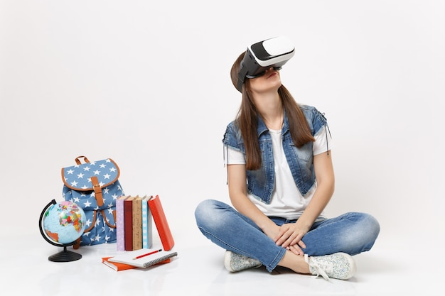 Young brunette woman student in virtual reality glasses looking up enjoying sitting near globe, backpack, school books isolated on white wall