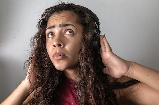 Young brunette woman surprise with high volume of headphones
