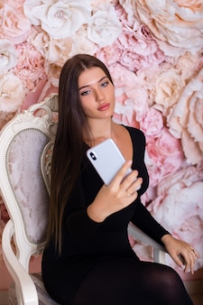 Молодая брюнетка женщина, делающая селфи по телефону