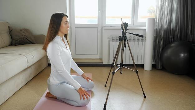 白いスポーツウェアの若いブルネットの女性トレーナーは、明るい部屋のソファの近くのマットの上に座っている三脚に携帯電話でビデオチュートリアルを撮影します
