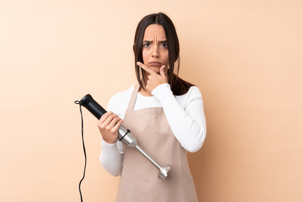 Young brunette woman using hand blender over isolated wall thinking