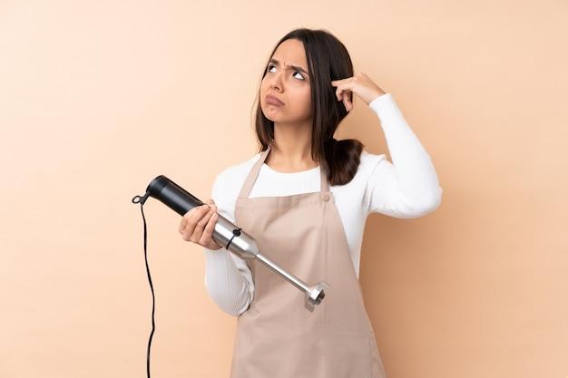 Молодая брюнетка женщина, используя ручной блендер над изолированной стеной, делая жест безумия, положив палец на голову