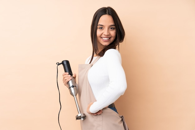 Young brunette woman using hand blender with arms crossed and looking forward