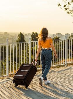 彼女の後ろに彼女のスーツケースを持って公園を歩いている若いブルネットの女性。