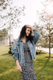 屋外でデニム ジャケットを着た若いブルネットの女性が笑顔