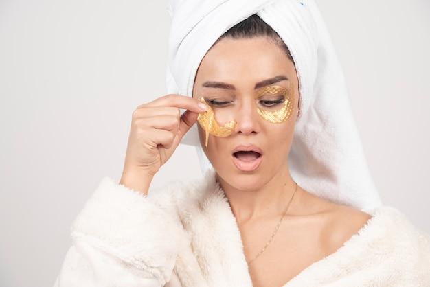 화장품 눈 패치를 적용하는 목욕 가운을 입고 젊은 갈색 머리 여자