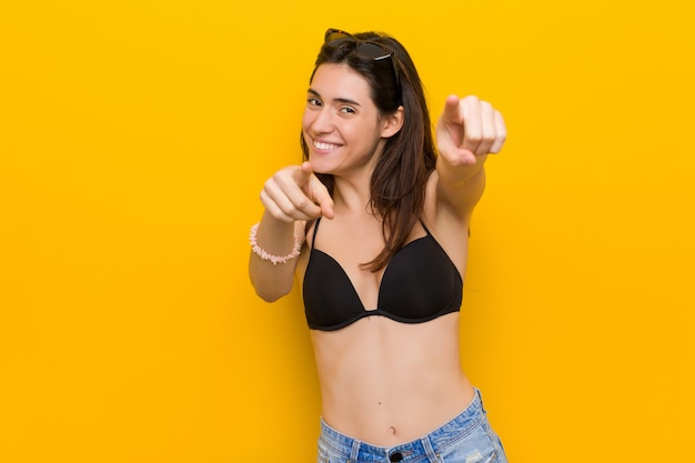 Young brunette woman wearing a bikini against yellow cheerful smiles pointing to front.