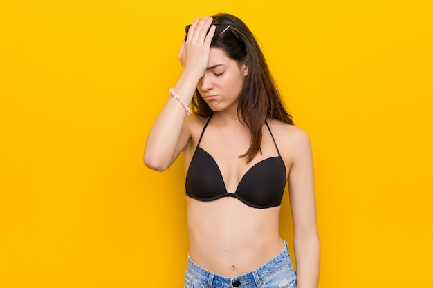 Young brunette woman wearing a bikini against yellow wall forgetting something, slapping forehead with palm and closing eyes