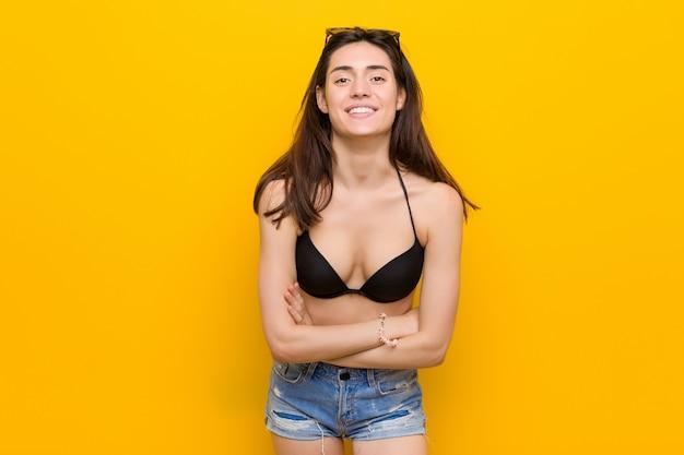 Young brunette woman wearing a bikini against yellow wall laughing and having fun.