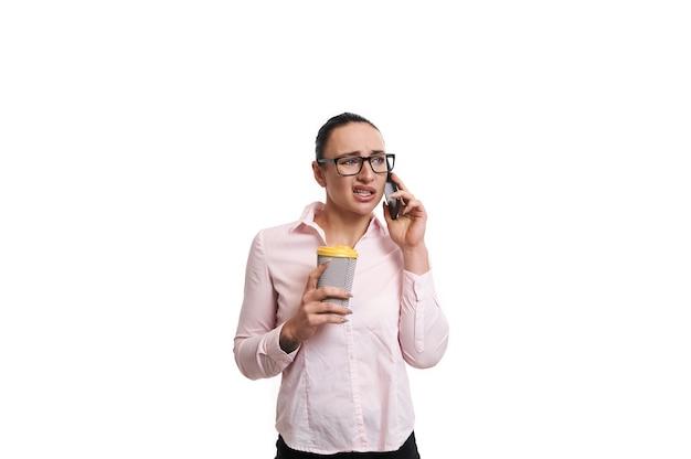 彼女の手に熱い飲み物と紙コップで携帯電話で話しているビジネスカジュアルな服を着ている若いブルネットの女性