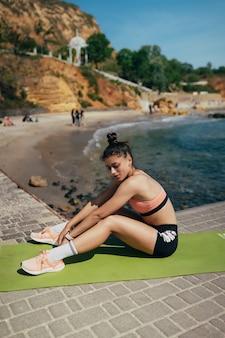 Giovane donna bruna che indossa abbigliamento fitness, che si estende sul materassino yoga fuori sul molo in estate.