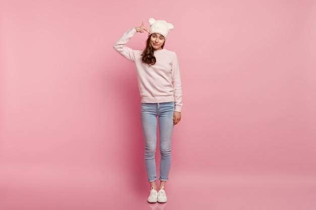 面白い帽子をかぶって若いブルネットの女性