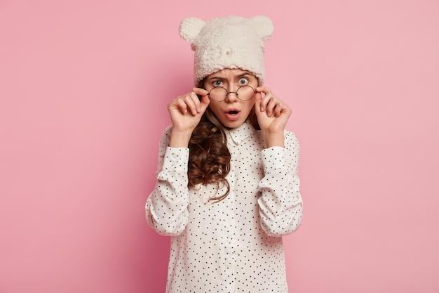 Giovane donna castana che porta cappello divertente