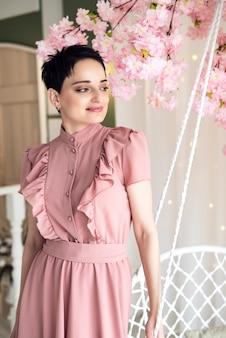 Молодая брюнетка в розовом платье стоит возле плетеных качелей, глядя в сторону