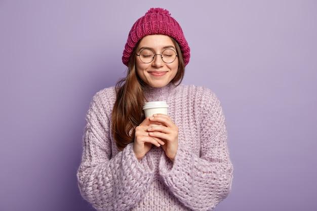 紫色のセーターを着て、コーヒーのカップを保持している若いブルネットの女性
