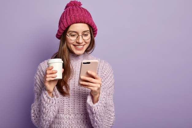 Young brunette woman wearing purple sweater and holding cup of coffee