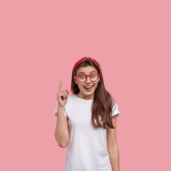 빨간 두건과 안경을 착용하는 젊은 갈색 머리 여자