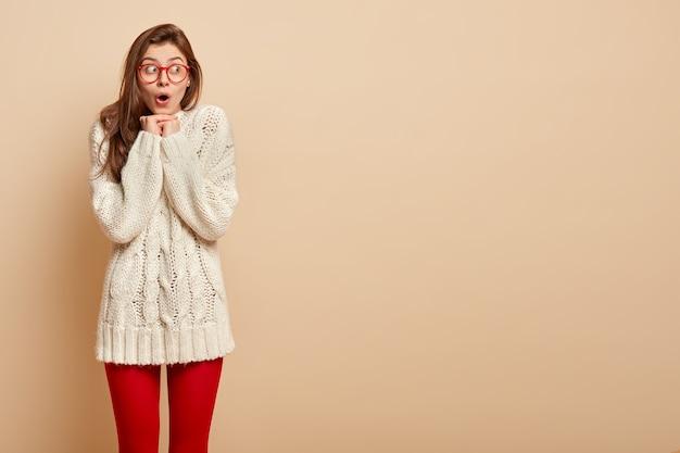 赤い眼鏡と白いセーターを着ている若いブルネットの女性