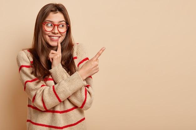 빨간 안경을 쓰고 젊은 갈색 머리 여자
