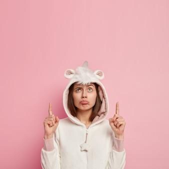 Молодая брюнетка женщина в пижаме единорог
