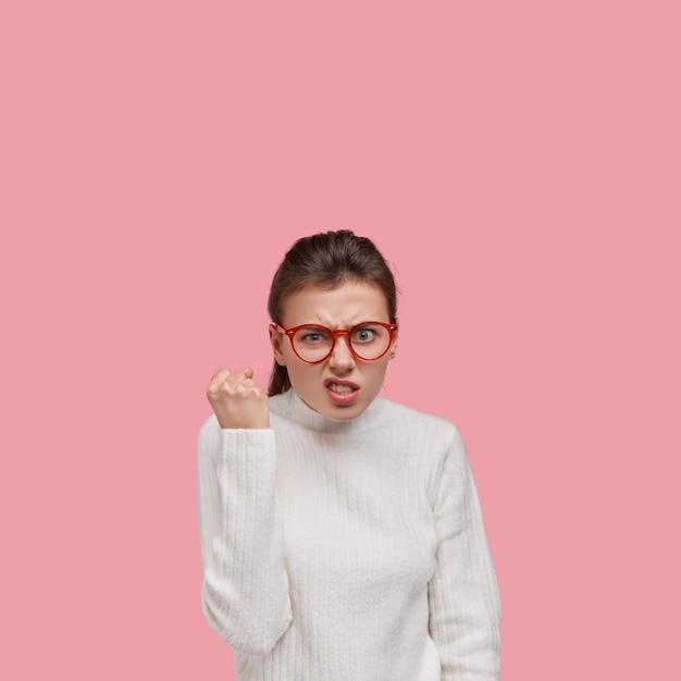 白いセーターと赤い眼鏡を身に着けている若いブルネットの女性
