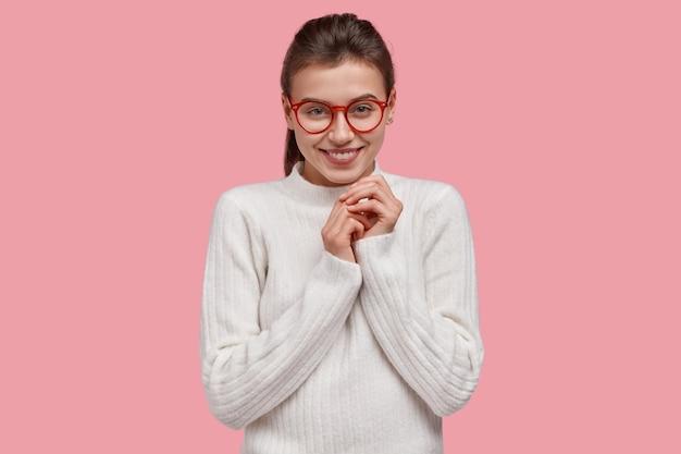 Giovane donna bruna che indossa un maglione bianco e occhiali rossi