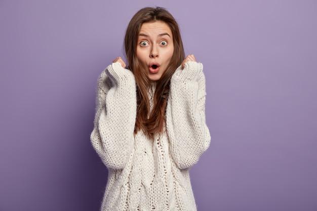 Giovane donna castana che indossa un maglione bianco
