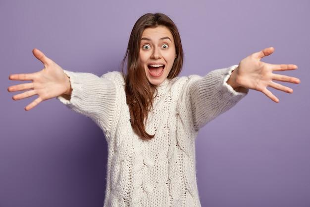 白いセーターを着ている若いブルネットの女性