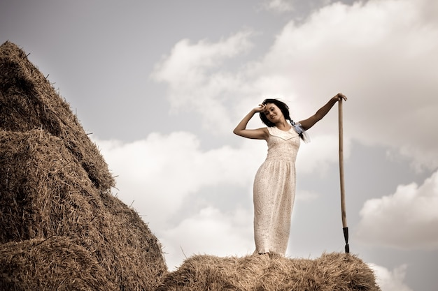 Young brunette woman in white dress standing with hay pitchfork