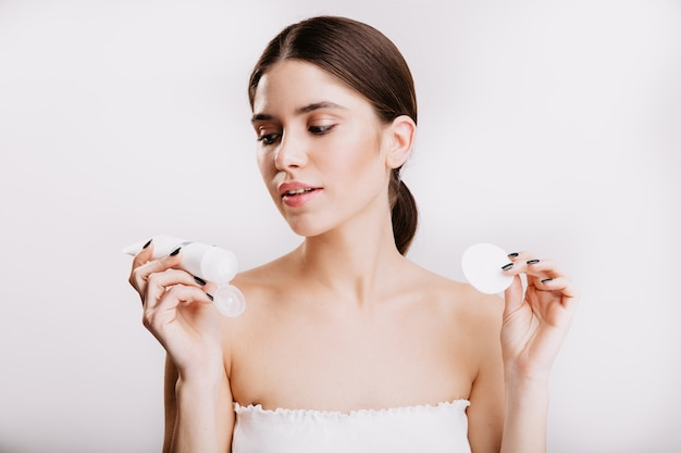 Young brunette woman in white top is looking at moisturizing face cream. portrait of model posing on isolated wall.