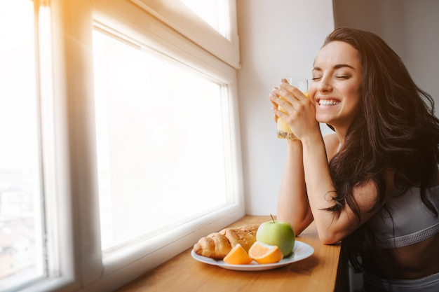 Young brunette woman in white underwear has breakfast by a wooden windowsill. a young female model eats.