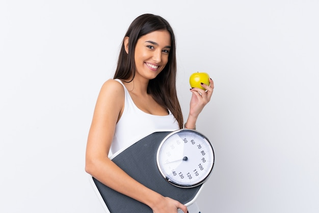 Young brunette woman over white with weighing machine and with an apple