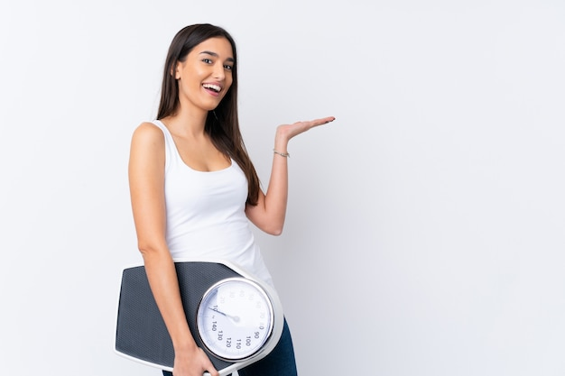 Young brunette woman over white with weighing machine