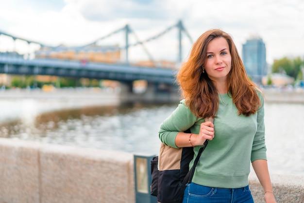 Молодая брюнетка с рюкзаком гуляет по набережной в москве