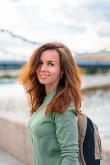 バックパックを持つ若いブルネットの女性はモスクワの堤防に沿って歩く