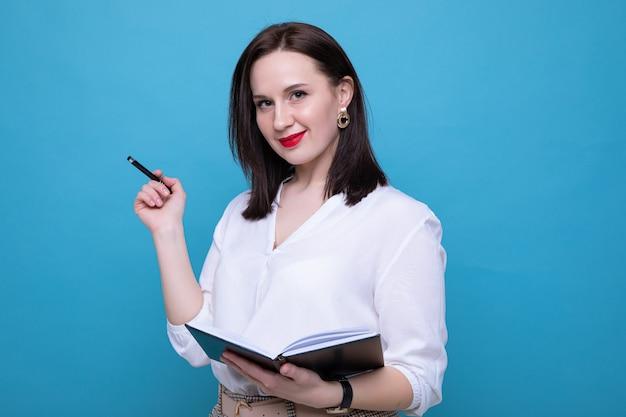 青い背景に日記とペンを持つ若いブルネットの女性