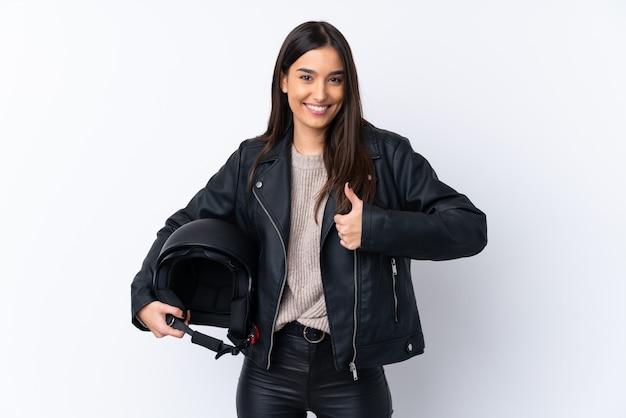 何か良いことが起こったため、親指で孤立した白い壁にオートバイのヘルメットを持つ若いブルネットの女性