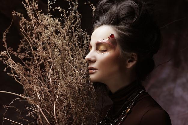 Молодая брюнетка женщина с ярким макияжем с сухими ветками