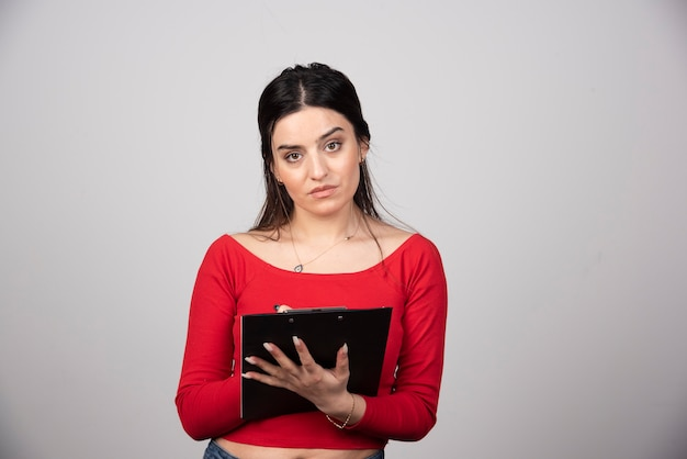 Young brunette woman with a clipboard looking at the camera.