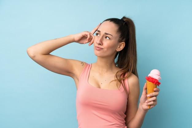 Young brunette woman with a cornet ice cream over isolated blue wall having doubts and with confuse face expression