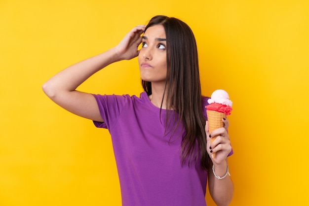 Young brunette woman with a cornet ice cream over isolated yellow wall having doubts and with confuse face expression