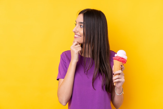 Young brunette woman with a cornet ice cream over yellow thinking an idea and looking side