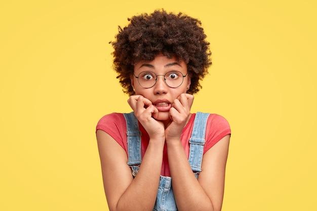Молодая брюнетка с вьющимися волосами и джинсовым комбинезоном