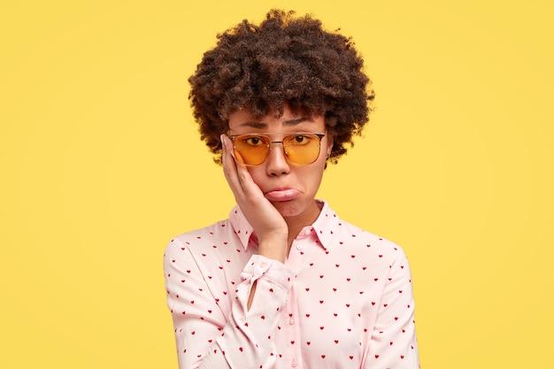 巻き毛と流行の眼鏡を持つ若いブルネットの女性
