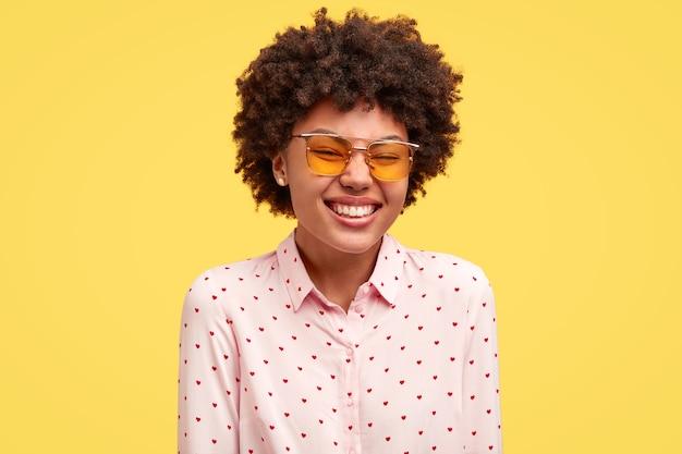 Giovane donna castana con capelli ricci e occhiali alla moda