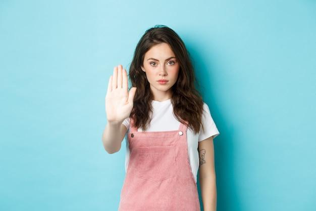 巻き毛の髪型の若いブルネットの女性は、ブロックジェスチャーで手を上げて、停止またはいいえと言って、悪い申し出を拒否し、何かを拒否し、青い背景に立っています。