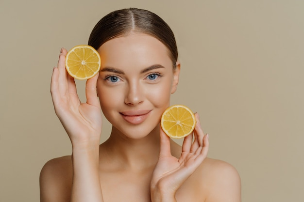 Young brunette woman with dark combed hair holds two slices of lemons